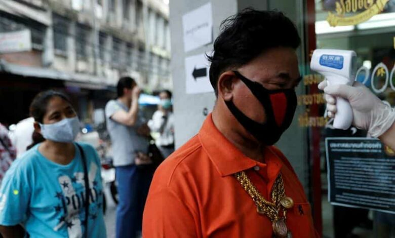 A man has his temperature checked before he is allowed in a goldsmith store as demand for cash increases after the partial shut down caused by the outbreak of the coronavirus disease hurts the local economy in Bangkok.