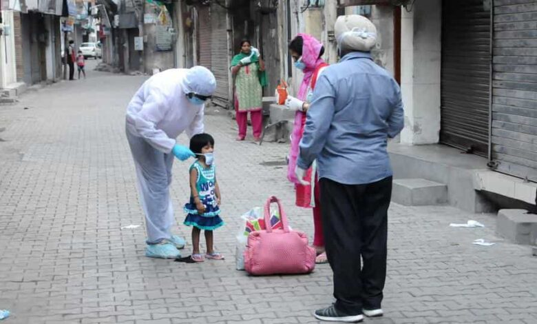 A medical worker in PPE ties a facemask to a child during the lockdown in Patiala, Punjab, on Saturday, April 16, 2020.
