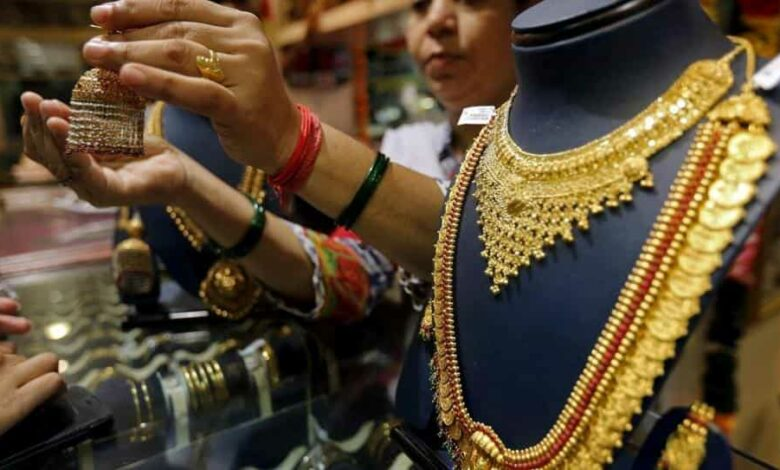 A saleswoman shows a gold earring to customers at a jewellery showroom in Mumbai, India.
