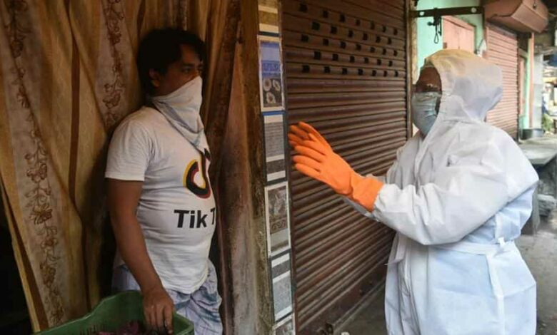 Health department staff in Personal Petective Equipment (PPE) suits collect data from a coronavirus hotspot during lockdown in India.
