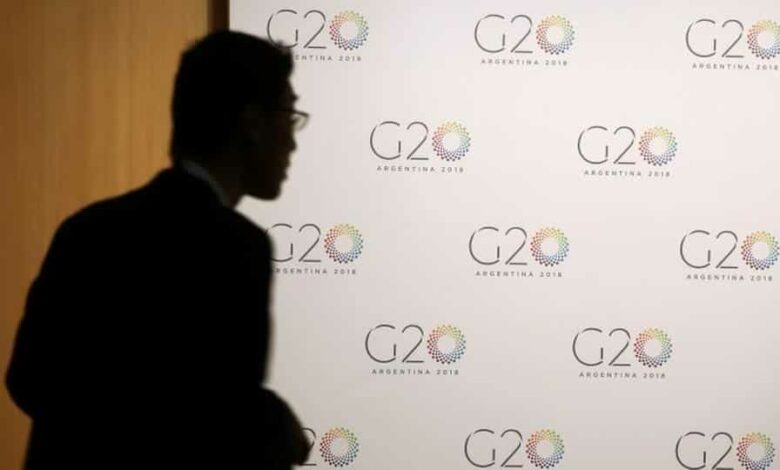 A man stands next to a board with the G20 Meeting of Finance Ministers logo.