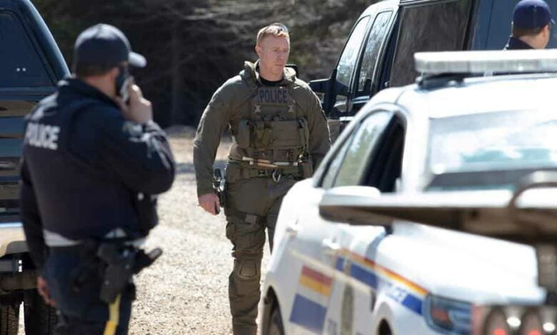 RCMP officers stand on Portapique Beach Road after Gabriel Wortman, a suspected shooter, was taken into custody and was later reported deceased according to local media, in Portapique, Nova Scotia, Canada April 19, 2020.