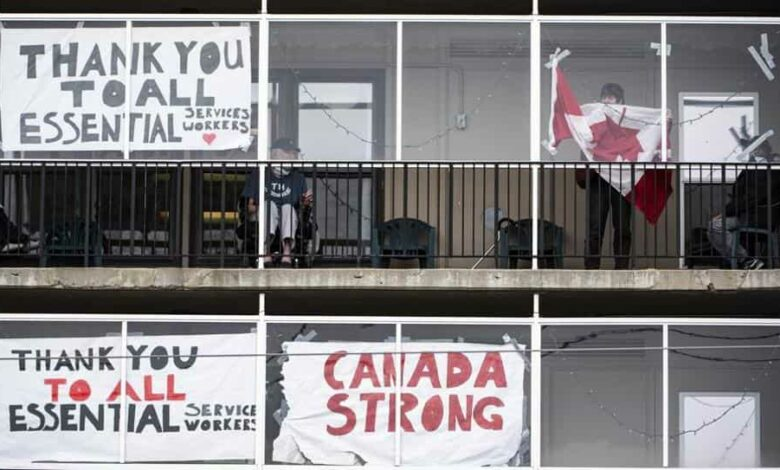 A resident untangles a Canadian flag in order to tape it back up to a window on a balcony at Laurier Manor, a long-term care facility experiencing an outbreak of Covid-19, Sunday, April 26, 2020, in Ottawa, Ontario.