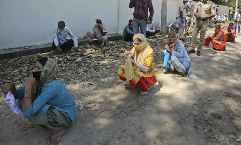People wait outside a bank to withdraw money during lockdown on the outskirts of Jammu on Wednesday.