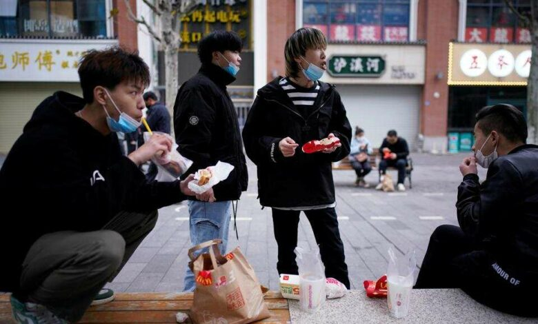 People with face masks eat outside a McDonald
