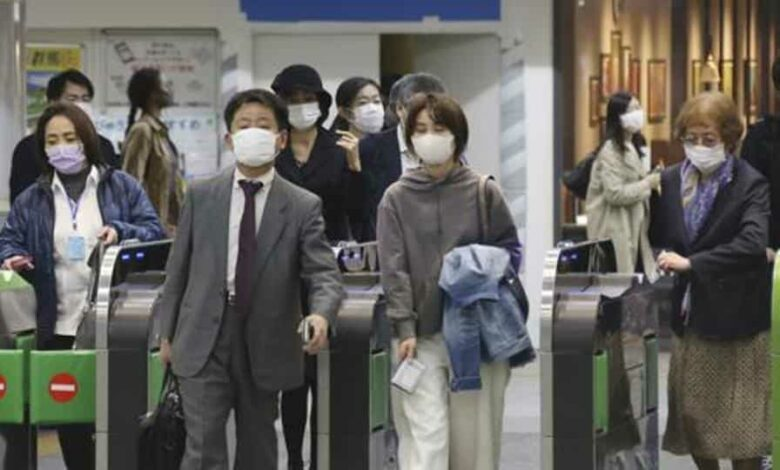 People wearing face masks to protect against the spread of the new coronavirus pass the gates at Yokohama station, near Tokyo, Wednesday, April 15, 2020.