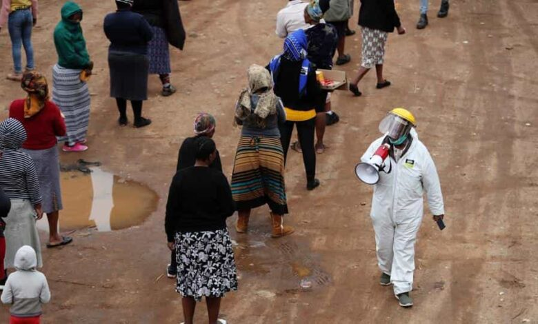 A man in protective clothing speaks trough a loudspeaker as he addresses locals queueing ahead of food distribution amid the spread of the coronavirus disease, in South Africa on April 28.