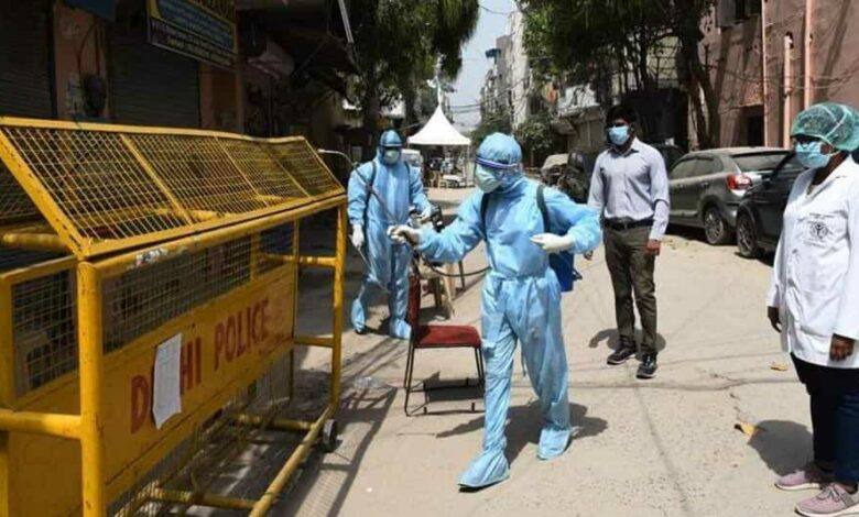 Health workers in Personal Protective Equipment (PPE) kit spray disinfectant to sanitize homes in Delhi's containment zones.