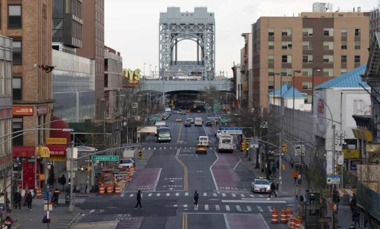 There is little traffic on 125th Street, Thursday, April 16, 2020, in the Harlem neighborhood of New York during the coronavirus pandemic. Gov. Andrew Cuomo extended stay-at-home restrictions Thursday through mid-May. (AP Photo/Mark Lennihan)