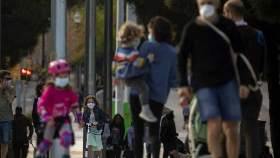 Families with their children walk along a boulevard in Barcelona, Spain, Sunday, April 26, 2020 as the lockdown to combat the spread of coronavirus continues.