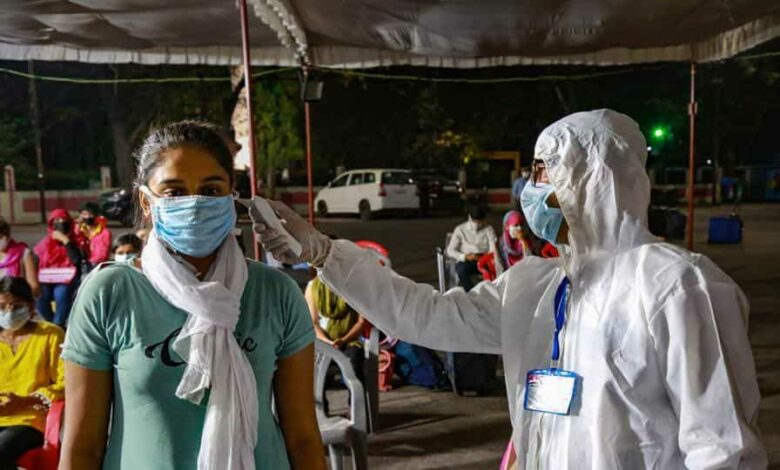 A medic checks the temperature of a student from Kota upon her arrival in Indore last week.