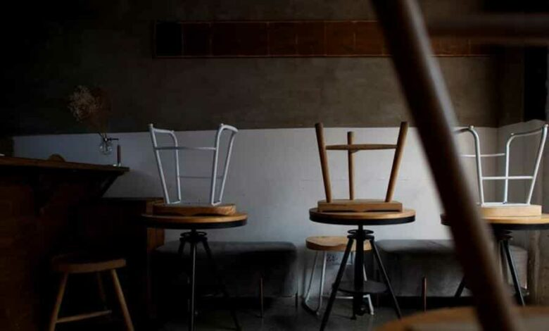 Stools are turned upside down in a cafe that is closed for regular business but open for takeout in the Wudaoying Hutong.