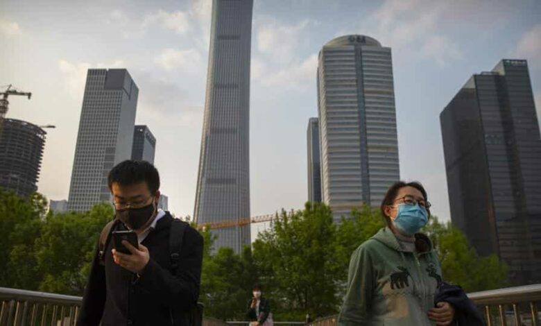 People wearing face masks to protect themselves against the spread of the new coronavirus walk across a pedestrian bridge in the central business district in Beijing.