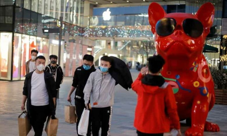People wearing protective masks walk in a shopping district, following an outbreak of the coronavirus disease (COVID-19) in Beijing, China.
