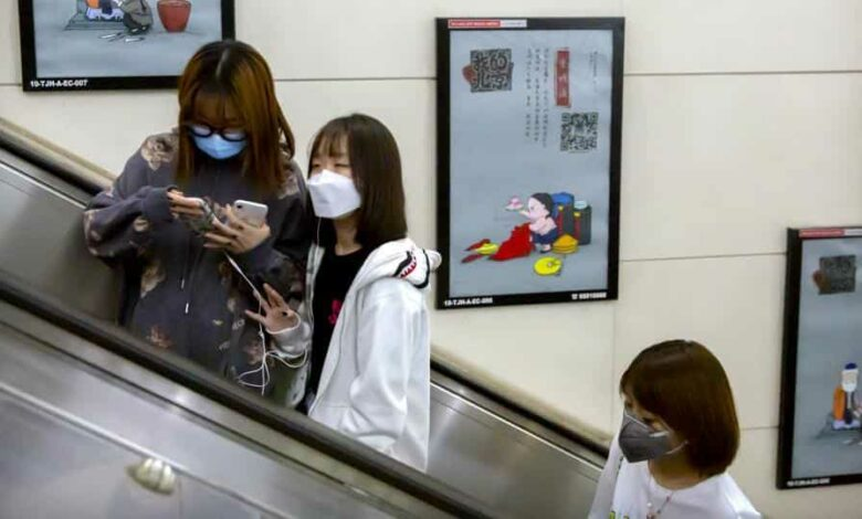 People wear face masks to protect against the spread of the new coronavirus as they ride an escalator in Beijing, on Wednesday.
