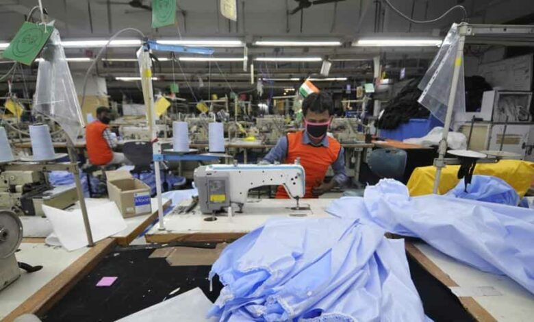 Workers stitch personal protective equipment (PPE) suits at a manufacturing unit in GB Nagar, on day eighteen of the 21 day lockdown to limit the coronavirus, in Noida.