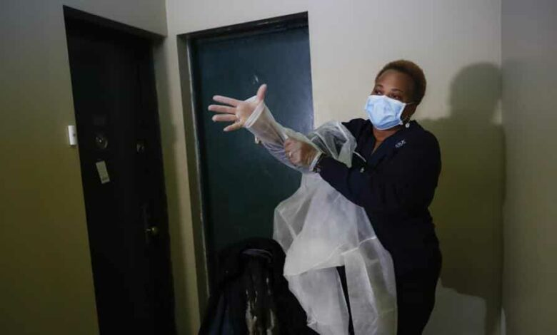 In this Thursday, April 23, 2020 photo, Ruth Caballero, a nurse with The Visiting Nurse Service of New York, puts on personal protective equipment before entering a patient