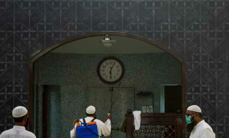 A worker (C) sprays disinfectant at a mosque ahead of the Muslim holy month of Ramadan during a government-imposed nationwide lockdown as a preventive measure against the COVID-19 coronavirus, in Karachi on April 22, 2020.