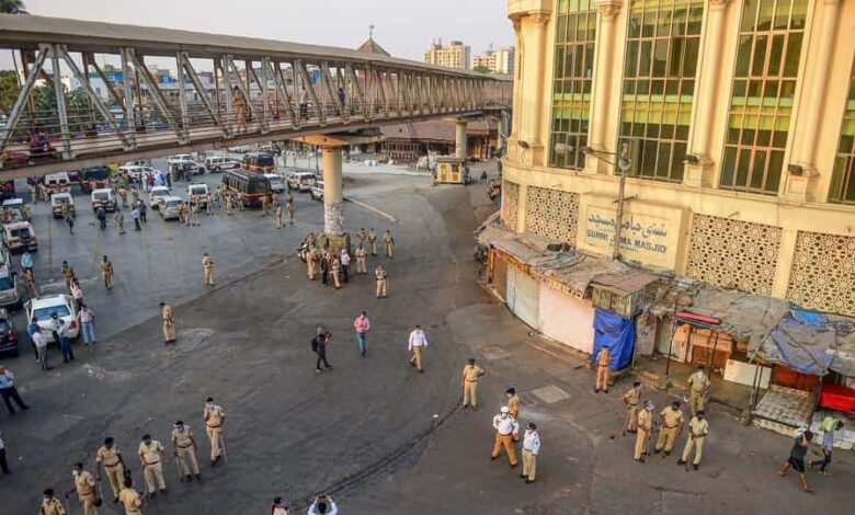 Police personnel stand guard after a crowd of migrant workers demanding transport arrangements for them to go back to their native places, was dispersed from the Bandra station on Tuesday.