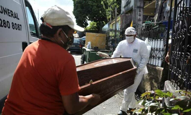 A relative and a worker of the Funeral SOS of the city of Manaus, wearing protective clothing, remove the coffin of Amadeu Garcia da Silva, 80, from his house amid the coronavirus disease outbreak, in Manaus, Brazil.