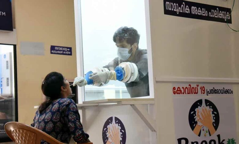 A staff member collects samples from people at a walk-in coronavirus testing kiosk at Ernakulam Medical Collage in Kochi on April 11.