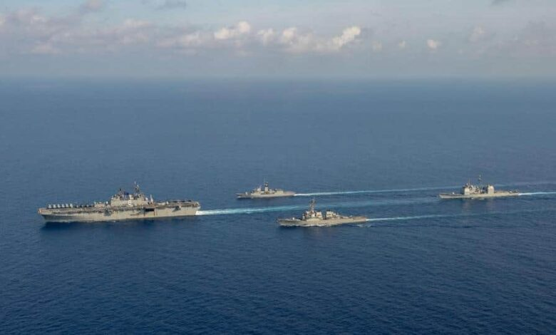 File photo: (L-R) Amphibious assault ship USS America, Royal Australian Navy helicopter frigate HMAS Parramatta, guided-missile destroyer USS Barry and guided-missile cruiser USS Bunker Hill conduct officer of the watch manoeuvres in the South China Sea, in this April 18, 2020 handout photo.