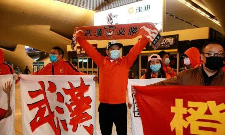 Fans of the Wuhan Zall football team welcoming the team members home.