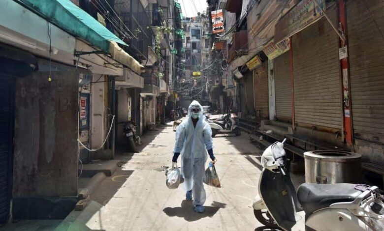 A South Delhi Municipal Corporation (SDMC) worker in a Personal Protective Equipment (PPE) suit while collecting garbage at J 4 Block of Khirki Extension in Khirki Village, one of the red zones now sealed, during lockdown against coronavirus, in New Delhi, India, on Wednesday, April 15, 2020.