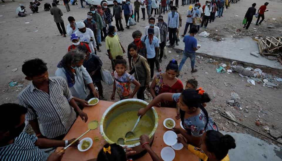 Migrant workers and homeless people stand in queue to receive free food during a nationwide lockdown to curb the spread of the coronavirus disease in India.