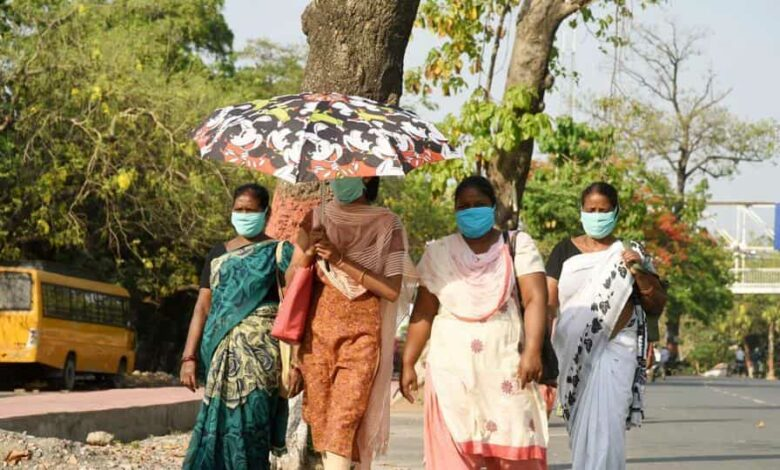 Women wearing  face masks seen using umbrella on a hot summer day, in Patna, Bihar,  May 13, 2020.