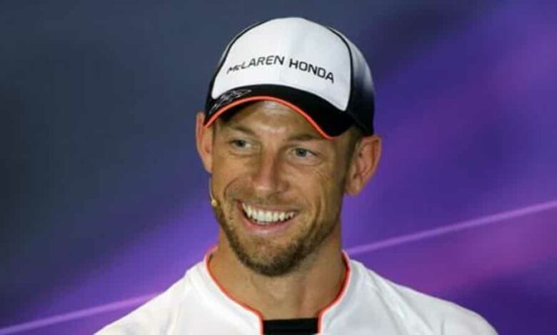 Jenson Button of Britain smiles during the news conference.