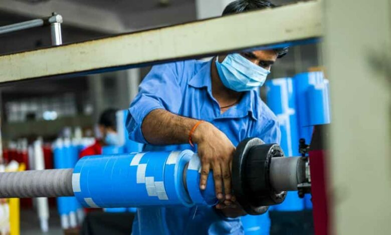 A worker wearing a protective mask operates a machine while producing adhesive sealing tapes at the Ajit Industries Pvt. factory in Sonipat district, Haryana.