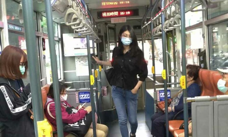 People wear face masks to protect against the spread of the new coronavirus as they ride on a bus in Taipei, Taiwan.