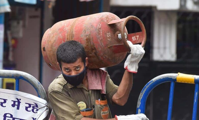 A worker carries LPG gas cylinder on his shoulder for delivery during the nationwide lockdown imposed in the wake of coronavirus pandemic, at Bhowanipore in Kolkata, Friday, April 24, 2020.