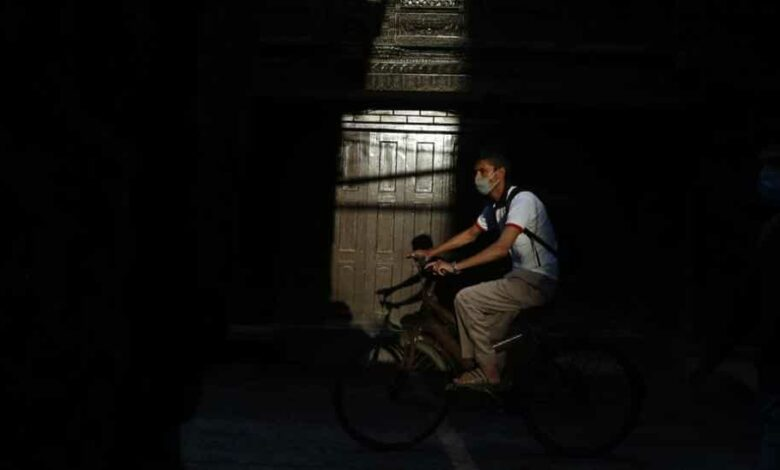 A man wearing face mask rides a bicycle during lockdown to control the spread of the new coronavirus in Kathmandu, Nepal, Monday, April 27, 2020.