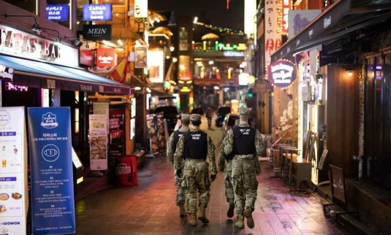U.S Army military police patrol the street at night in the Itaewon area of Seoul, South Korea, on Saturday, May 9, 2020.