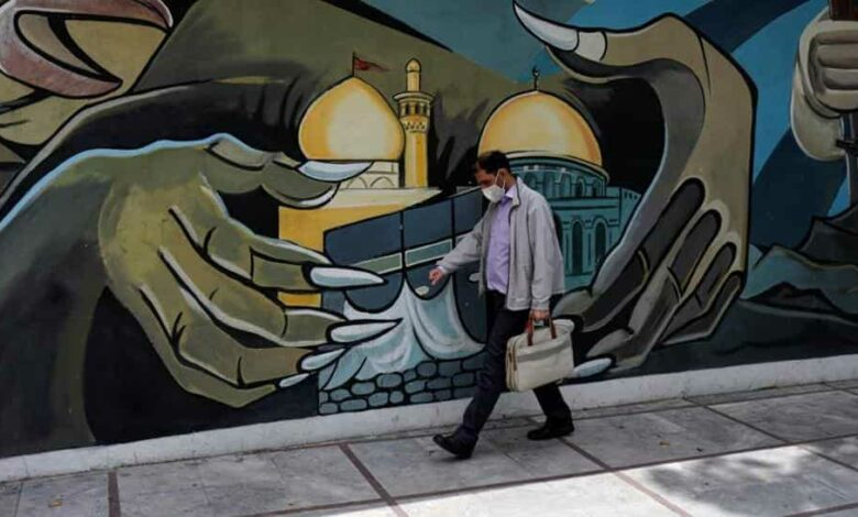 A man wearing a protective face mask walks past a Palestine mural on the wall following the outbreak of the coronavirus disease (Covid-19), in Tehran, Iran, April 30, 2020.