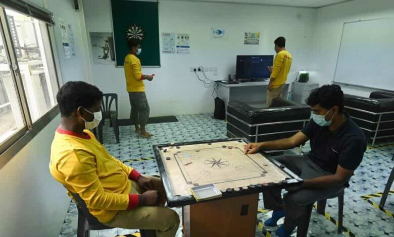 Workers, who have been registered as providing essential services during the Covid-19  pandemic, play carrom in their temporary living quarters during a media tour in Singapore on May 5, 2020.