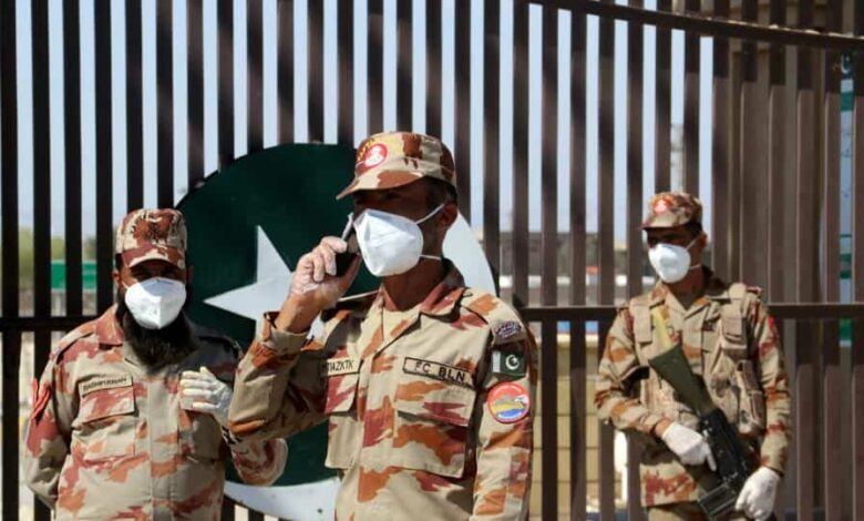 Paramilitary soldiers wear face masks as they stand in front of a closed gate of Pakistan