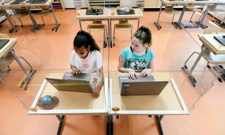 FILE PHOTO: Pupils sitting behind partition boards made of plexiglass attend a class at a primary school, during the coronavirus disease (COVID-19) outbreak, in Den Bosch, Netherlands, May 8, 2020.