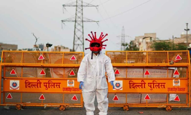 An artist wearing a coronavirus-shaped helmet and a protective suit stands next to a police barricade as he requests people to stay at home during an extended lockdown to slow the spread of the coronavirus disease (Covid-19) in New Delhi.