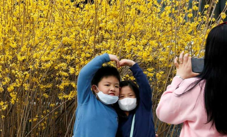 Children wearing masks to prevent contracting the coronavirus pose for photographs in downtown Seoul.