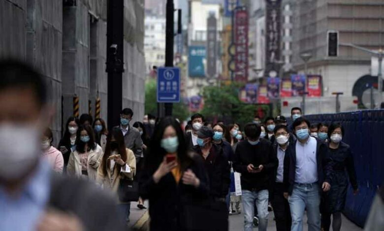 People wearing face masks to protect themselves from Covid-19 walk at a main shopping area in Shanghai.
