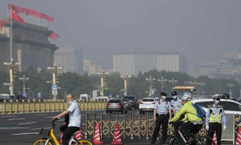 Cyclists ride past policemen blocked the cycling path leading to the Great Hall of the People and Tiananmen Square, Beijing.