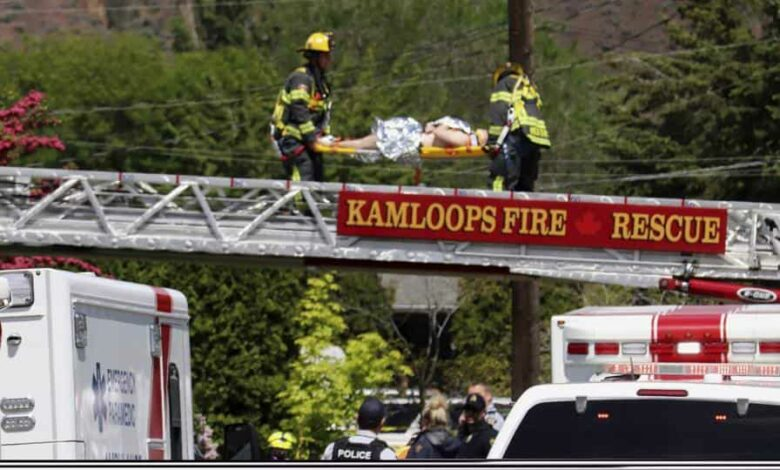 First responders carry an injured person on a stretcher across a fire truck ladder from a rooftop at the scene of a crash involving a Canadian Forces Snowbirds airplane in Kamloops, British Columbia, Sunday, May 17, 2020.