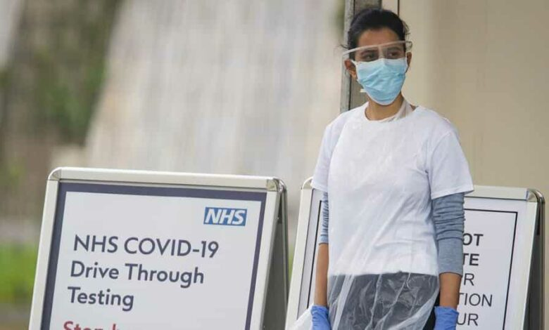 A medical worker waits at a drive-in coronavirus testing facility at the Chessington World of Adventures Resort in Chessington, England.