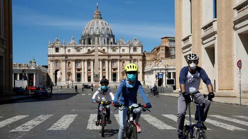 People wearing protective face mask bike in front of St. Peter