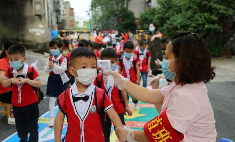 A staff member takes body temperature measurement of schoolchildren at a kindergarten that has resumed operation after Covid-19 lockdown was lifted in China, in Hunan province on May 11.
