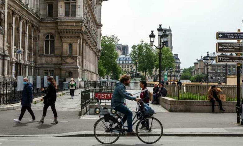 A cyclist passes the Metro station on Rue de Rivoli as France enters a new phase of lockdown easing measures, in Paris, France, on Monday, May 11, 2020.