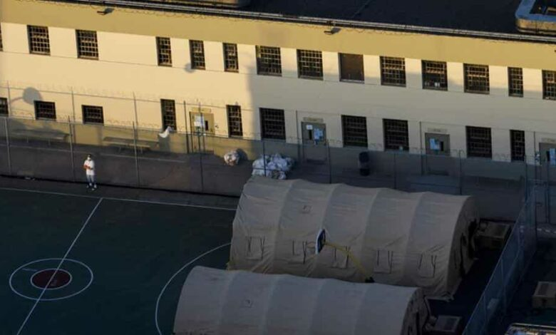 A inmate wears a face mask while standing outside of tents at the Federal Correctional Institute (FCI) Terminal Island prison in this aerial photograph taken above Los Angeles, California, U.S., on Friday, May 1, 2020. ]